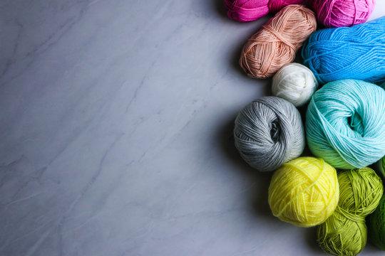 Colorful yarn balls on light grey background