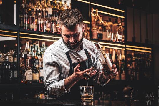 Diligent happy barman is preparing alcoholic beverege for customer.