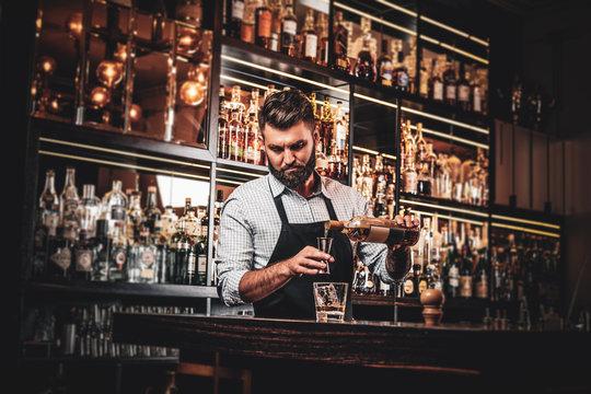 Serious barman is prepairing drinks for customers at posh bar.