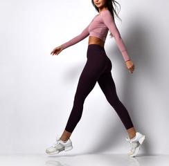 Sporty woman legs walking in sport wear on a white