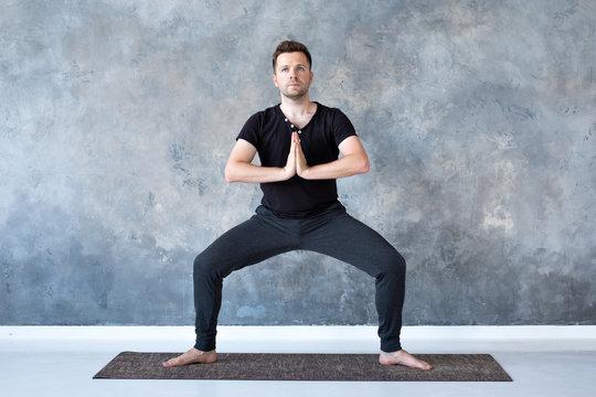Man working out, yoga, pilates, fitness training, Goddess Pose or rudrasana