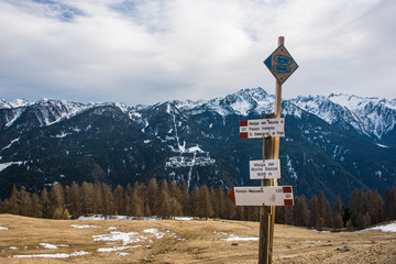 Tourist signs in Italian Alps - directions and snowshoes, snow rackets. Snow-capped mountains at the background. The Brenta Dolomites, Trento, Italy
