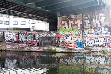 Hackney, East London, England, UK - April 2019: Murals and graffiti below a railway bridge along Regent's canal near Broadway Market, East London