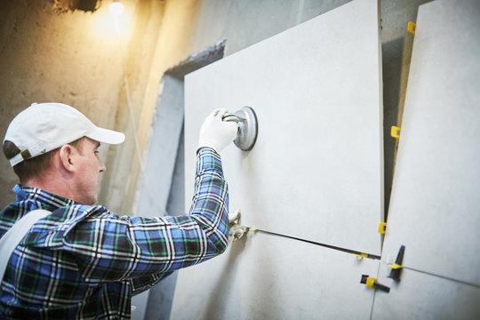Tiler installing large format tile on wall. home indoors renovation