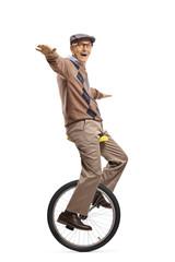 Senior man riding a mono-cycle and balancing with hands