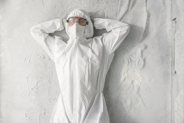 A man in white protective uniform, respirator and plastic transparent glasses. Wall mural