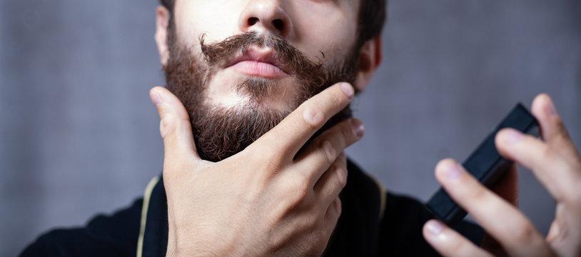 Bearded guy puts a tool on the beard. Studio gray background.