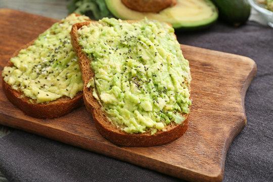 Tasty avocado toasts on wooden board