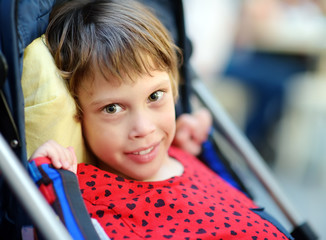 Portrait of a cute little disabled girl in a wheelchair. Child cerebral palsy. Inclusion.