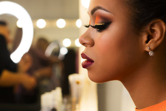 Close-up portrait young woman African American with perfect skin and radiant make-up in orange-coloured shades. Sensitive profile. Beauty industry. Space for text.