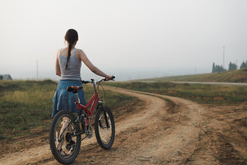 white caucasian young woman in casual clothing walking with bike on village road, view from back in full body size, lifestyles stock photo image