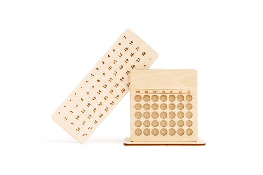 Wooden perpetual calendar made of light wood with pencil stand isolated on white background.