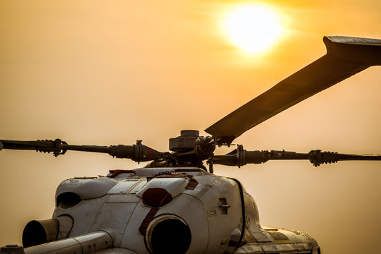 Close up airplane propeller, the Military helicopter parking landing on offshore platform with sun sky background.