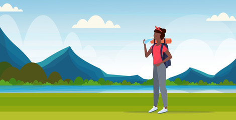 woman hiker with backpack drinking water african american girl traveler on hike hiking concept mountains landscape background full length flat horizontal Wall mural