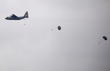 Singapore Armed Forces paratroopers jump out of a C130 aircraft in their parachutes, during a training exercise, in Singapore