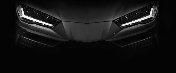 Silhouette of black sports car with LED headlights on black background