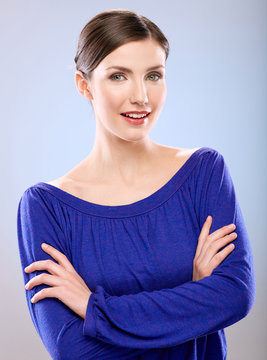woman in blue dress portrait with crossed arms.