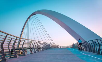 Young man riding bicycle through Dubai water canal bridge, Beautiful Architecture Design