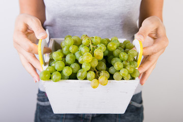 White basket with green grapes. basket with grapes in the hands of a woman. Grape Harvesting Fototapete