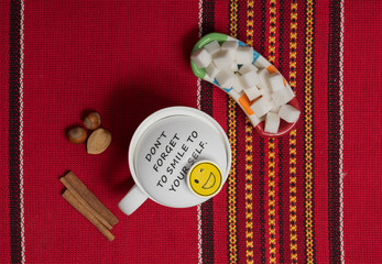 Top shot of white mug with a positive quote saying Do not forget to smile to your self, cinnamon sticks, hazelnut, and almond on a background of red ornate tablecloth