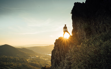 Man explorer standing on cliff alone mountain summit and enjoying sunrise. Beautiful moment the miracle of nature