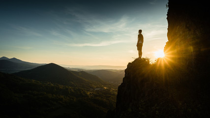Silhouette of the person on the high rock at sunset. Satisfy hiker enjoy view. Tall man on rocky cliff watching down to landscape. Vivid and strong vignetting effect. Wall mural
