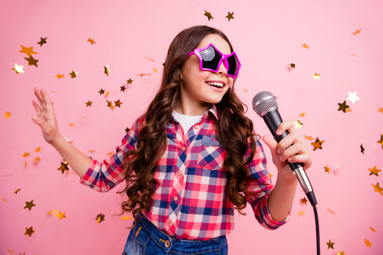 Close up photo of cool attractive crazy lady kid have fun visit event future musician loud voice solo hold hand free time stylish checked shirt isolated over pink background long haircut hairdo