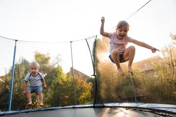 Kids jumping high on trampoline