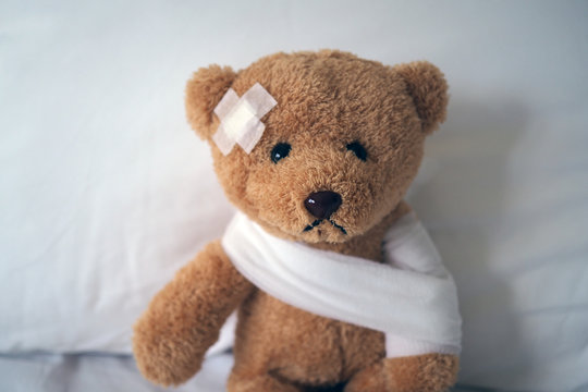 Sad bear doll lying sick in bed with the wound on the head and bandage