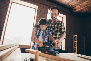 Low angle view of two nice smart clever creative cheerful person master builder dad fixing creating repairing building cabinetry restoration at modern studio loft industrial brick interior indoors