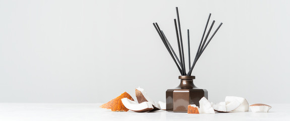 Aroma reed diffuser bottle home fragrance with rattan sticks with the scent of coconut and the freshness of the tropics on white background. Long wide banner with copy space.