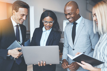 Diverse businesspeople smiling while discussing work on a laptop
