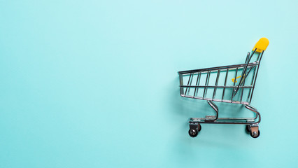 Shopping cart on blue background. Top view or flat lay. Shop trolley at supermarket as sale,...