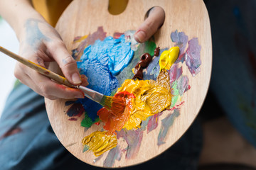 Fine art school. Closeup of artist hands holding wooden palette, mixing acrylic paint with brush. Wall mural