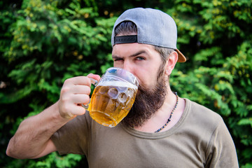 Enjoying his alcoholic beer. Bearded man drinking alcoholic drink in summer. Hipster with alcoholic beverage on nature. He is a beer drinker not an alcoholic