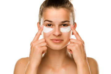 A young woman applying cream under her eyes on white background