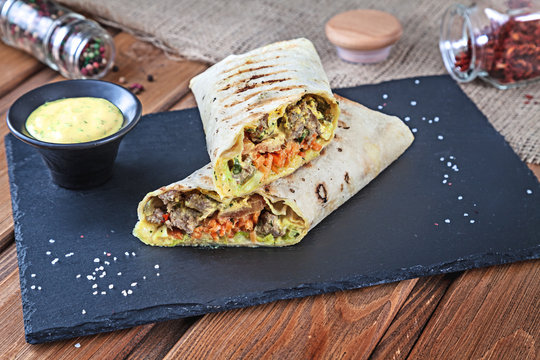 Close up view on Shawarma sandwich, gyro fresh roll in lavash. Shaurma served on black stone. Kebab in pita with copy space. Traditional Middle Eastern snack, fast food. Horizontal close up