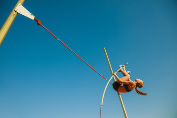 Professional female pole vaulter training at the stadium in sunny day. Fit female model practicing in high jumps outdoors. Concept of sport, activity, healthy lifestyle, action, movement, motion. Wall mural