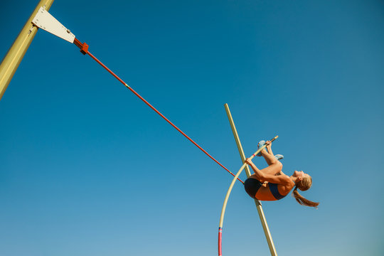 Professional female pole vaulter training at the stadium in sunny day. Fit female model practicing in high jumps outdoors. Concept of sport, activity, healthy lifestyle, action, movement, motion.