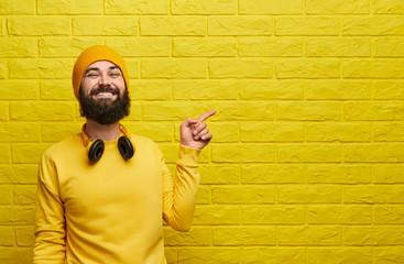 Cheerful hipster pointing at yellow wall Wall mural