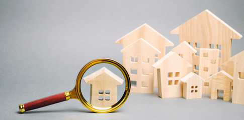 Fototapeta Magnifying glass and wooden houses. House searching concept. Home appraisal. Property valuation. Choice of location for the construction. Search for housing, apartments. Real estate appraiser services obraz