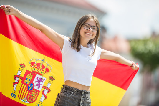 Happy girl tourist walking in the street with spanish flag