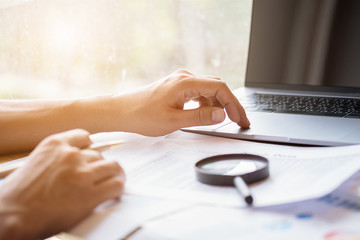 man looking through a magnifying glass to documents. Business assessment and audit. Magnifying glass on a financial report. Close-up Of Checking Bills With Magnifying Glass.Concept of search.