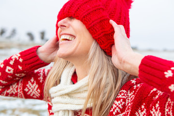 Happy woman outdoors pulling beanie over eyes