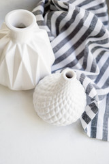 Two white ceramic vases and striped cloth on white background