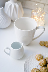 Simple white mug and a creamer on white table with cookies