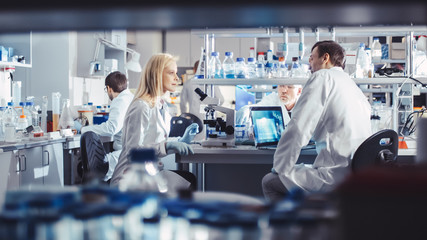 Group of Research Scientists in White Coats are Working and Having Discussion in a Modern High-Tech Laboratory. Genetics and Pharmaceutical Studies and Researches.