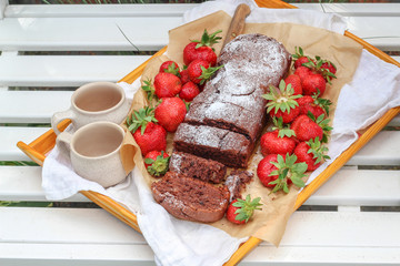 Homemade cake and fresh strawberries  on a white garden bench
