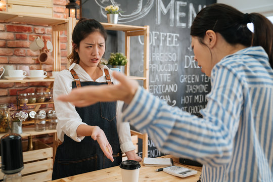 emotional female customer arguing with staff girl at bar counter. Unsatisfied visitor angry about service in cafe shop. woman client dislike coffee drink and yelling at barista lady in morning store