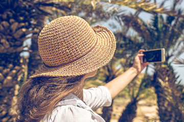Woman in the straw hat taking selfie picture or video using smartphone in the palm forest. Seychelles islands